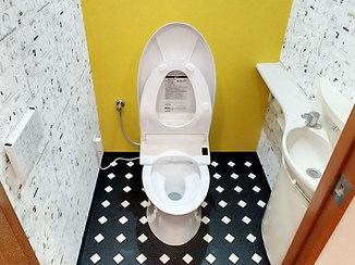 トイレリフォーム スヌーピーのシンプルな壁紙にアクセントカラーが映える、ローシルエットのトイレ
